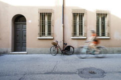 Old Italian bicycle. Red old Italian bicycle on sunlight. Ancient buildings Royalty Free Stock Images