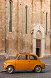 Old Italian Car in Front of a Catholic Church. Classic Orange Italian Car in Front of a Catholic Church Stock Images