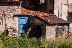 Old italian house in disrepair with blue door. And garden Stock Images