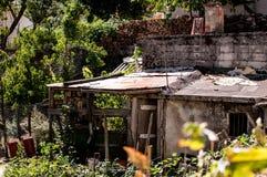 Old italian house in disrepair with garden abandoned. Garbage in the garder, windows and door broken Stock Photos
