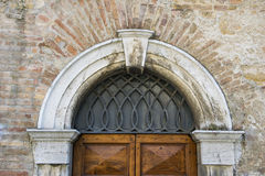 Old Italian house textured door with stone arch facade Stock Photography