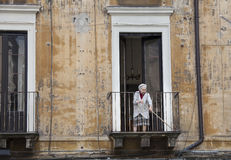 Old italian lady sweeping balcony. Catania, Sicily. Italy Royalty Free Stock Photos