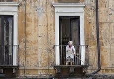 Old italian lady sweeping balcony. Catania, Sicily. Italy royalty free stock photos
