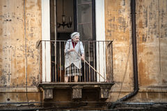 Old italian lady sweeping balcony. Catania, Sicily. Italy Royalty Free Stock Image