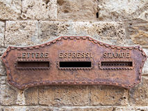 Old italian mailbox oxidized. In the wall Royalty Free Stock Image