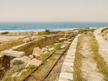 Old Italian railroad tracks among ancient Roman ruins on the Mediterranean coast of Libya at Leptis Magna royalty free stock photo