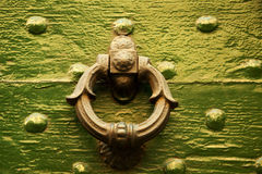 Old Italian round shape door knocker on green wood. Detail of an old gold Italian door knocker in the shape of a floral motive ring on a green wood background royalty free stock photos
