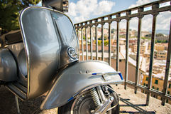 Old Italian scooter  on a viewpoint of the city of Genoa, Italy. Particulars of an old style scooter with the city on background Stock Images