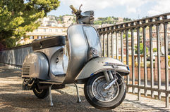 Old Italian scooter  on a viewpoint of the city of Genoa, Italy. Particulars of an old style scooter with the city on background Royalty Free Stock Photo