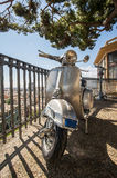 Old Italian scooter  on a viewpoint of the city of Genoa, Italy. Particulars of an old style scooter with the city on background Stock Photography