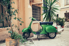 Old Italian street. Green scooter leaning against a wall in Italy Royalty Free Stock Photo