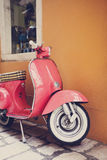 Old Italian street. Pink scooter leaning against a wall in Italy Stock Image