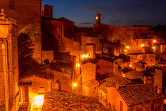 Street Lights in the Night Sorano. Old Italian town of Sorano at night. Street lights illuminate the roofs of old houses stock image