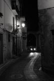 Old Italian Village Street. Nighttime view of an old italian street with a car lighting the road surface Royalty Free Stock Photos