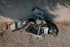 Old trash jacket thrown on the street on asphalt royalty free stock photography