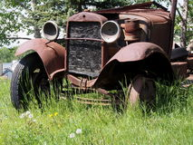 Old Jalopy Rusting Away In Tall Grass Royalty Free Stock Photography