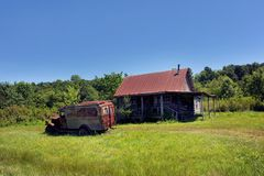 Arkansas Nostalgia. Old jalopy sits in yard of abandoned log cabin in the Ozark Mountains of Arkansas.  Cabin has tin roof and old truck has faded sign saying Royalty Free Stock Images
