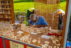 Old Japanese artisan, wooden work concept. Asakusa, Tokyo, JAPAN - Aug. 16 2017: An old Japanese craftsman working with wood, creating wooden figures in the Royalty Free Stock Photography