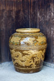Old Japanese glazed earthenware or ceramic jar with dragon pattern design used as water container Stock Image