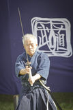 Old Japanese man playing martial arts in traditional customes Royalty Free Stock Image