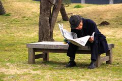 Old Japanese Man sits in park and reads the daily Newspaper Royalty Free Stock Photography
