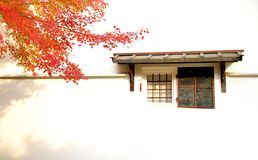 Old japanese warehouse window and maple tree in autumn color Stock Photo