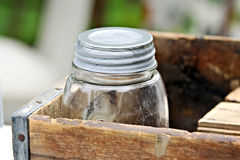 Old Jar in Box. Old glass jar in a wooden box stock photos