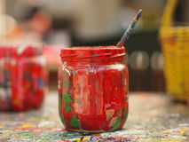 Old jar covered with red paint and brush. Tools for painter royalty free stock image