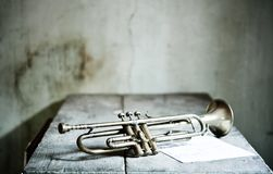 A beautiful jazz trumpet from the 40s with a new musical score over an old wooden table. The old jazz trumpet player Stock Photography