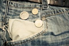 Old jeans and australian dollars coins vintage. Old jeans and australian dollars coins near empty pocket Stock Photo
