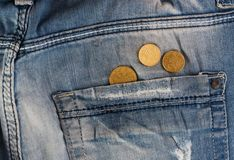 Old jeans with coins in pocket Stock Photo
