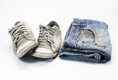 Old Jeans and old shoes. Different blue jeans isolated on white background Stock Photography