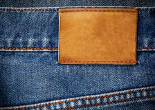 Old jeans texture with leather label background Stock Photos