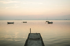 Old jetty with anchored rowing boats in the water Stock Image