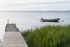 Old jetty and an anchored small boat Stock Photography