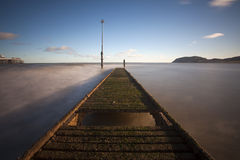 Old jetty with moving tide Royalty Free Stock Image