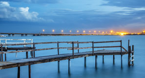 Old Jetty on a River with City Lights in the Background Stock Photos