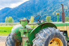 Old John Deere tractor with rusty, dirty machine parts. Sitting on a farm. Large tractor wheels showing. Worn out logo on the farm royalty free stock photos