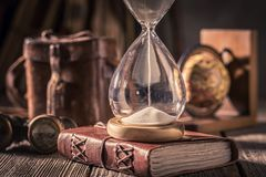 Old journal and hourglass with binocular, compass and books. On old table royalty free stock photography