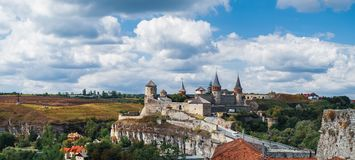 Kamianets-Podilskyi Castle in Ukraine. Old Kamianets-Podilskyi Castle under a cloudy blue sky. The fortress located among the picturesque nature in the historic stock photo