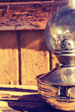 Old kerosene lamp on the background of old wooden yellow wall Stock Photos
