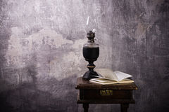 Old kerosene lamp and open book Royalty Free Stock Photos