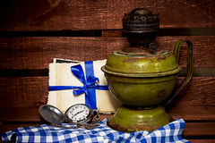 Old kerosene lamp and a pocket watch Royalty Free Stock Image