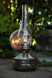 Old kerosene lamp stands on the ground, outdoors Royalty Free Stock Photos