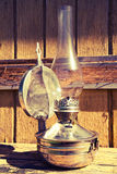 Old kerosene lamp stands on wooden surface, outdoors, toning Stock Image