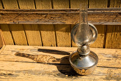Old kerosene lamp stands on wooden surface, outdoors Stock Photo