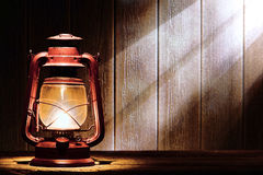 Old Kerosene Lantern Lamp in Rustic Country Barn. Old fashioned kerosene lantern style oil lamp burning with a soft glow light in an antique rustic country barn Royalty Free Stock Photography