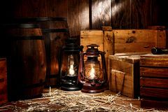 Old Kerosene Lantern Lamps in Antique Warehouse. Old fashioned light kerosene lantern style oil lamps burning in an antique shipping warehouse stockroom with Royalty Free Stock Image