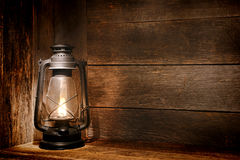 Old Kerosene Lantern Light in Rustic Country Barn. Old fashioned vintage kerosene oil lantern lamp burning with a soft glow light in an antique rustic country Royalty Free Stock Image