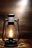 Old Kerosene Lantern Light in Rustic Country Barn. Old fashioned rustic kerosene oil lantern lamp burning with a soft glow light in an antique country barn with Royalty Free Stock Images